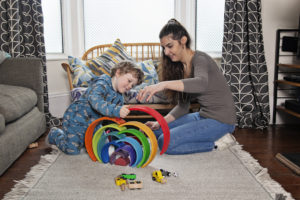 Nanny and boy playing with rainbow toy