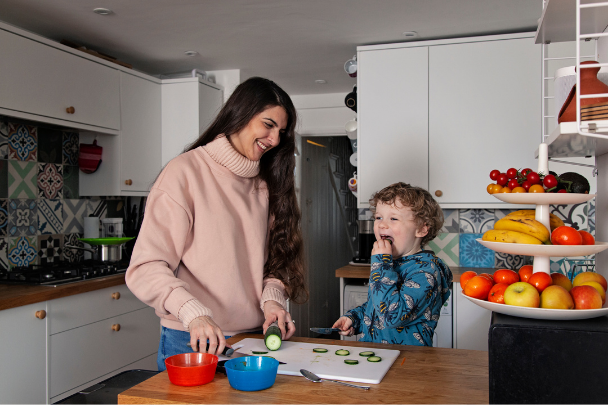 Childminder chopping vegetables in the kitchen with a child