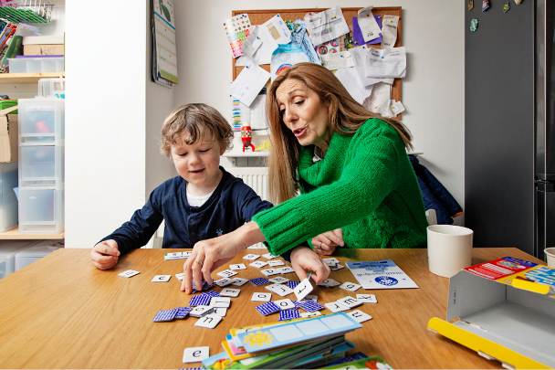Childminder helping child spell with letters and games