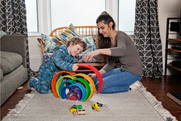 Childminder and child playing with rainbow blocks in a house