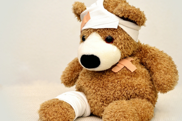 Teddy bear with bandages and plasters on his head and arms