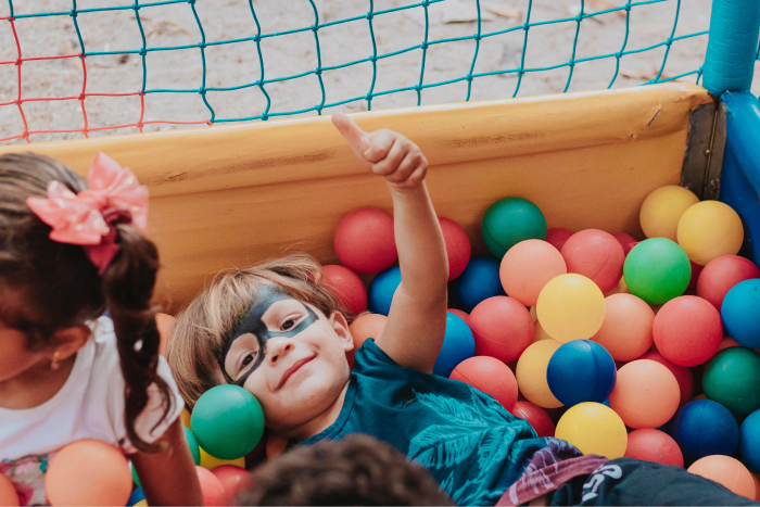 Children playing in a colourful ball pit