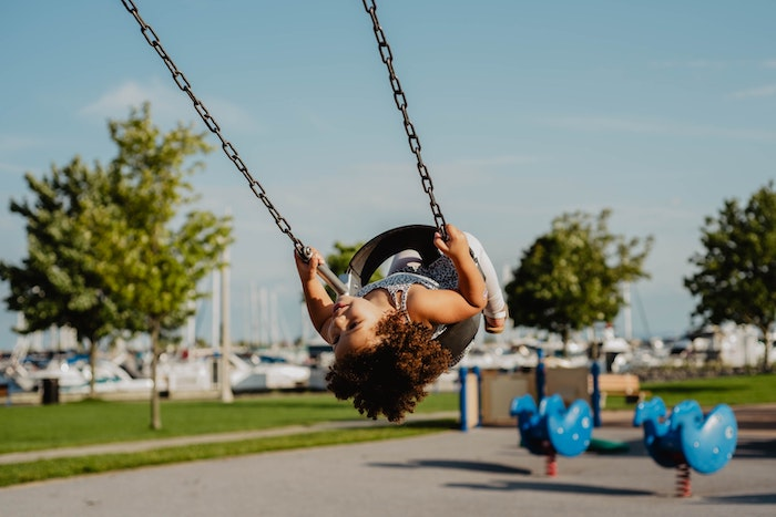 Child being pushed on the swing by their childminder