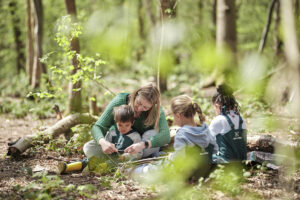 Childminder sitting and playing with children in the forest