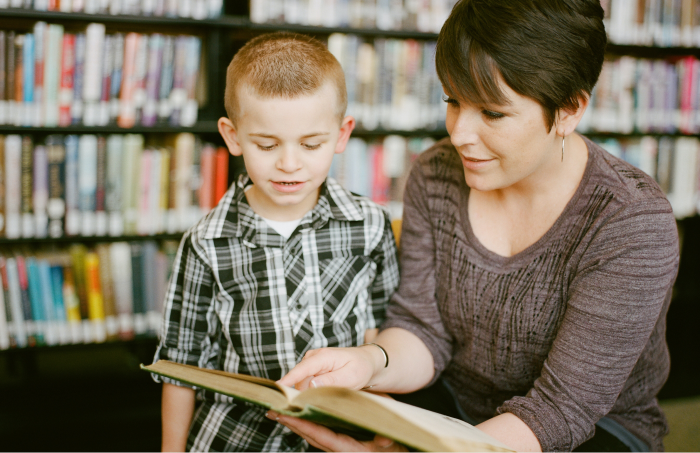 A childminder shows a book to a boy she is looking after
