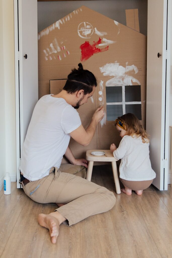 A childminder helping a child to paint in their home
