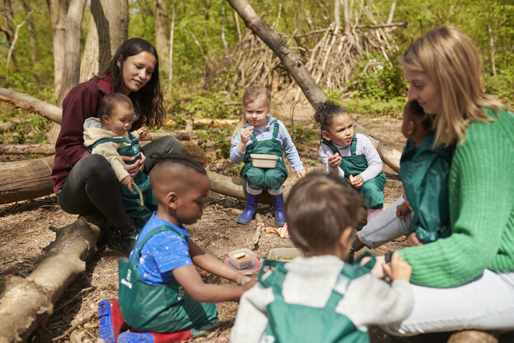 childminder who used to be a teacher teaches a class outside in the forest
