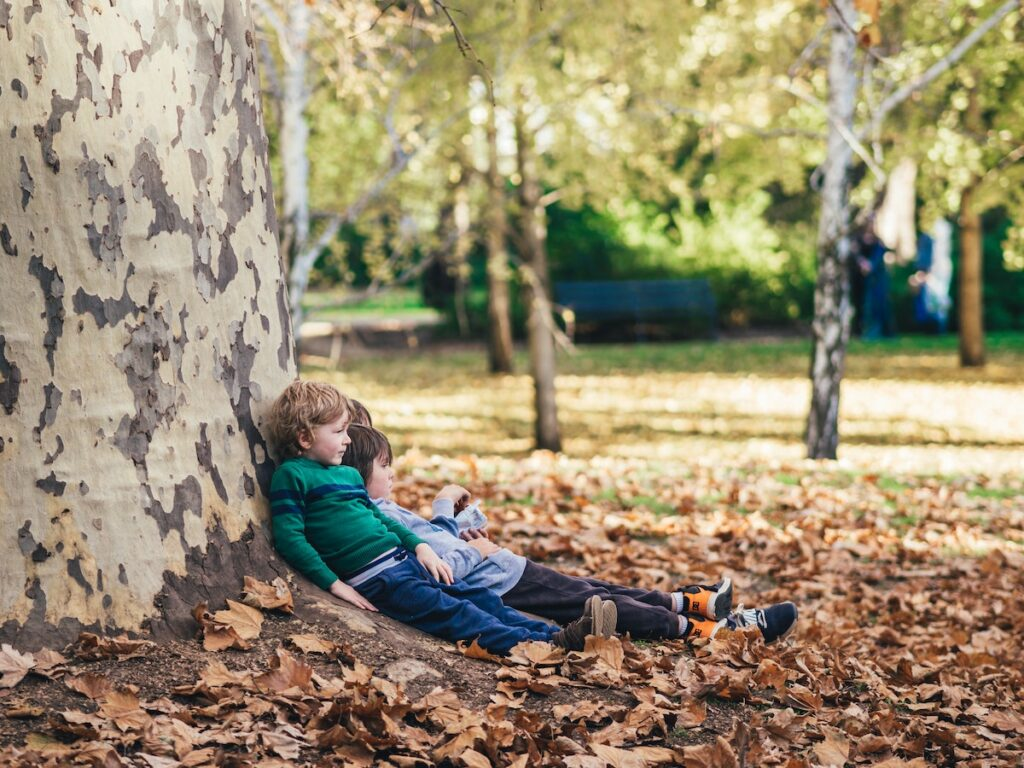 Two children leaning up against a tree outside in the park with their childminder