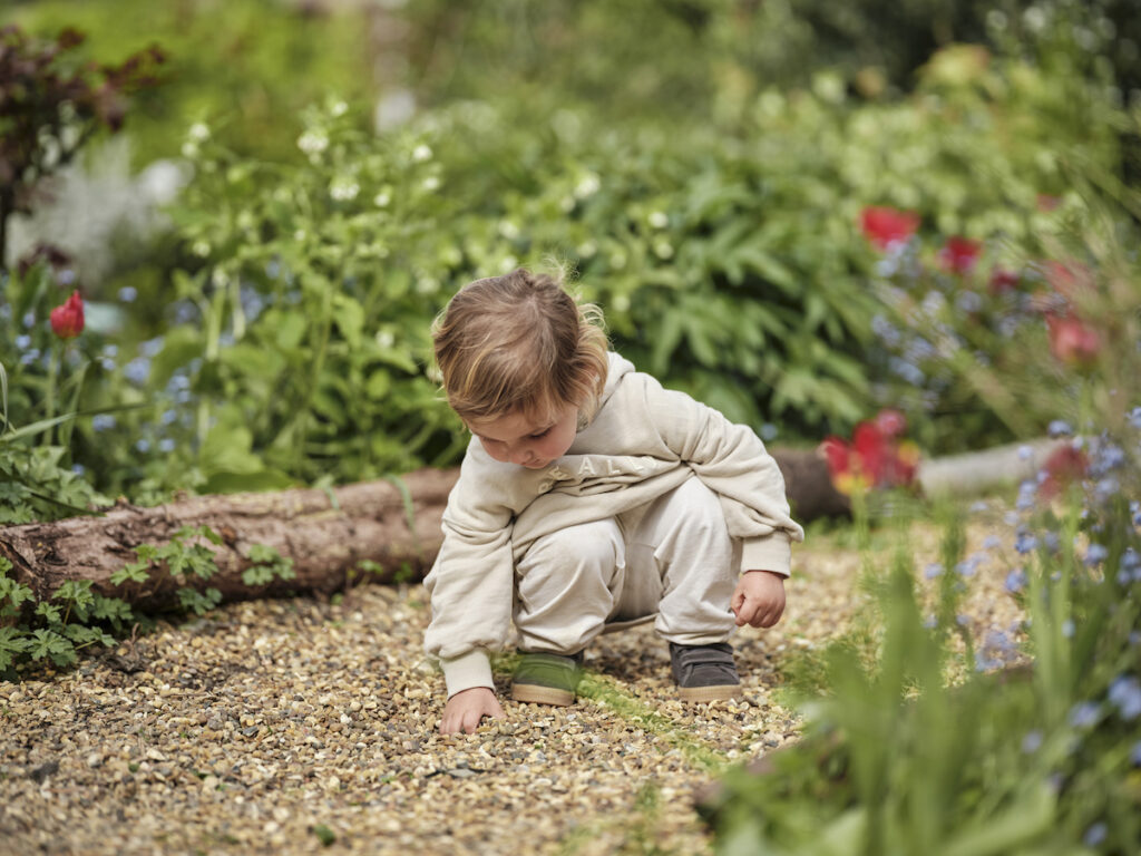 Child playing outdoors in nature with childminder caring for them