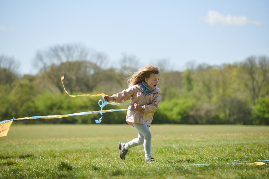 Child running in field with a colourful Koru Kids kite