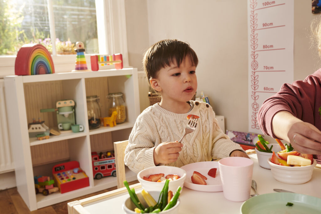 Childminder feeding children healthy food at the dinner table