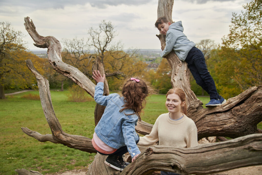 Nanny caring for two young children as they climb trees and play outside