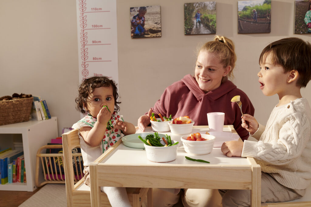 A childminder sitting at the dinner table eating food with two children