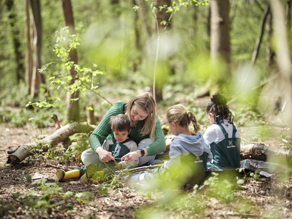 Childminder teaching children about leaves sitting outside in the forest
