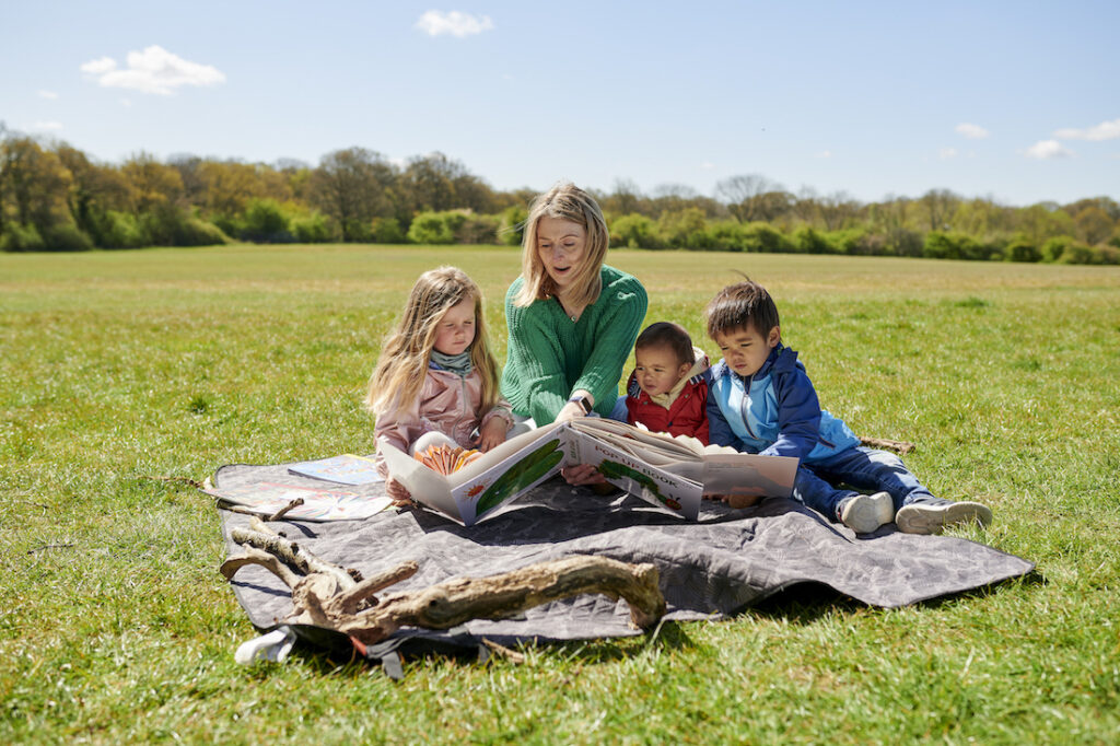Teacher sits on grass with preschool children reading books outside as a childminder
